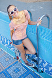 a beautiful young girl with a skateboard on the pool ladder