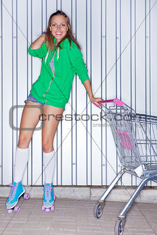 a beautiful young girl in roller skates near supermarket trolley