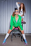 two beautiful young girls play supermarket trolley near the wall