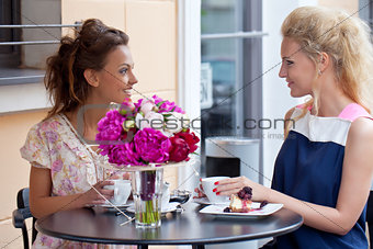 two beautiful young girls in summer outfit sitting at the table