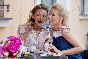 two beautiful young girls in summer outfit have lunch at the tab