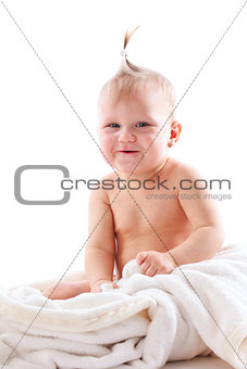 adorable baby playing with white blanket