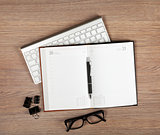 Blank notepad with pen and glasses