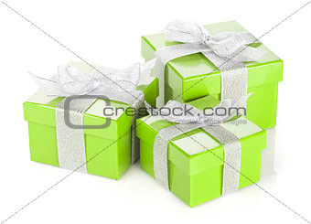 Three green gift boxes with silver ribbon and bow