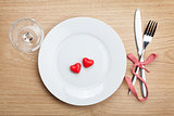 Valentine's Day heart shaped candy over plate with silverware an