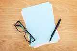 Blank lined paper with office supplies and glasses