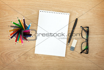 Blank notepad with office supplies and glasses