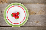 Ripe strawberries on plate over wooden table background