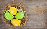 Easter eggs nest on wooden background
