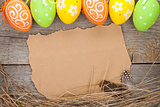 Easter eggs and paper for your greetings on wooden background