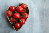 fresh red delicious tomatoes  in the heart shape wooden plate on