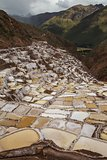 View of Salt ponds, Maras. Peru, South America with Andes and cloudy sky in the background