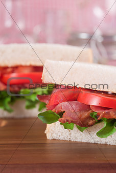 Fresh BLT on white sandwich in rustic kitchen setting