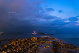 Stunning landscape with storm and lightning dawn with rocky coas