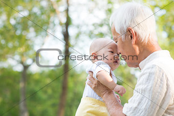 Asian grandfather kissing grandson