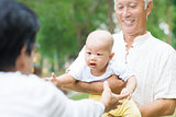 Asian grandparents playing with grandchild