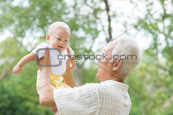 Asian grandfather carrying grandson