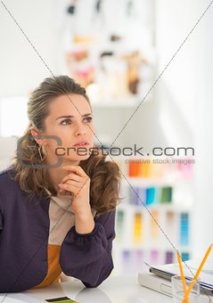 Portrait of thoughtful fashion designer in office