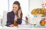 Happy fashion designer talking phone in office