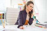Concerned fashion designer talking phone in office