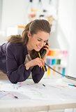 Smiling fashion designer talking phone at work