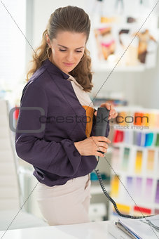 Thoughtful fashion designer with phone in office