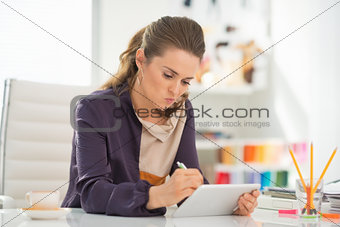 Fashion designer working on tablet pc in office