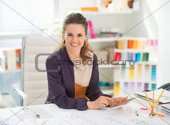 Happy fashion designer with tablet pc in office