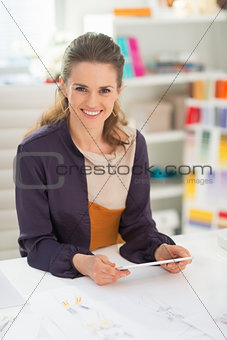 Portrait of happy fashion designer with tablet pc in office