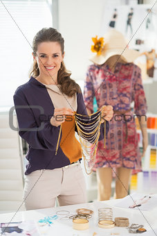 Happy fashion designer choosing accessories in office