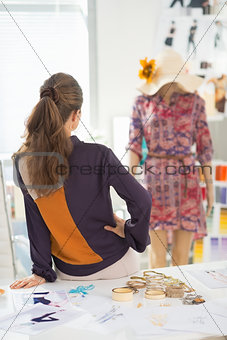 Fashion designer looking on mannequin. rear view