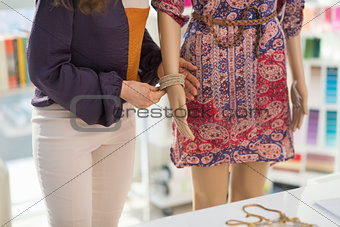 Closeup on fashion designer decorating mannequin