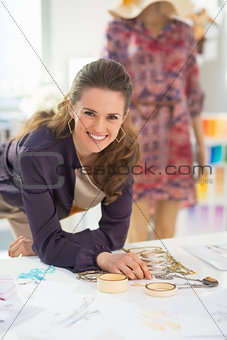 Happy fashion designer choosing accessories for garment