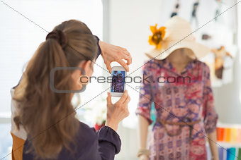 Fashion designer taking photo of mannequin