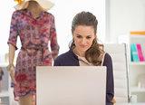 Fashion designer working on laptop in office