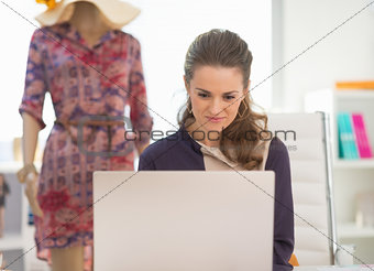 Fashion designer working on laptop in office