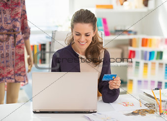 Fashion designer with credit card using laptop