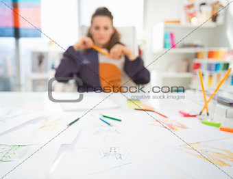 Closeup on table and thoughtful fashion designer in background