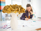 Closeup on vase of flowers on table and fashion designer working
