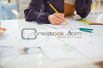 Closeup on fashion designer working in office