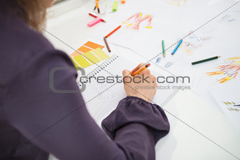 Closeup on fashion designer making sketches. rear view