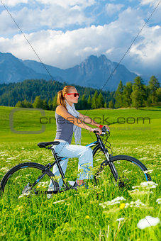 Active woman on bicycle in mountains