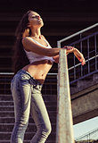 Sexy young woman in shirt and jeans stands on stairs at sunset time