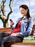 Smiling woman using smartphone on park bench