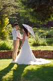 Bride and groom in garden wedding with parasol