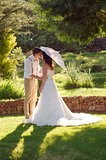Bride and groom kissing in garden wedding