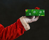 Santa Father Christmas hand with wrapping paper present and red star ribbon decoration on blackboard background