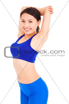 Beautiful fit woman stretching her arm and smiling