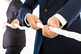 Two businessman work together and playing tug of war