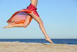 Woman legs jumping on the beach happy